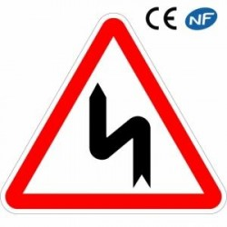 Panneau routier ATTENTION suite devirages dontle1er estàgauche (A1d)